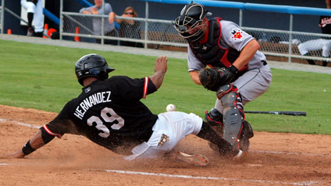 Michel Hernandez slides home with Norfolk's second run Tuesday.